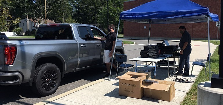 Pennsbury Technology Director, Timothy McCleary (right) and Supervisor of Educational Technology, Brad McCormick (center) worked with parents and students in need of swapping out Chromebooks on the first day of school.